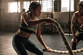 Female exercising with battle ropes at the gym with coach. Athlete doing battle rope workout at gym with trainer.