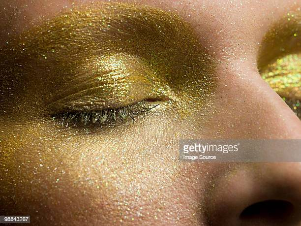 Femme yeux maquillage or couvert dans