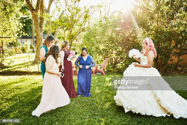 Female family members preparing for quinceanera photos in backyard