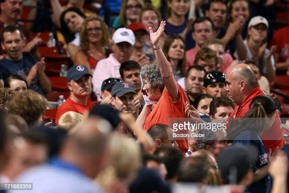 A female fan who was hit in the head by a foul ball while seated behind home plate waves to the crowd to acknowledge the cheers she is receiving as...