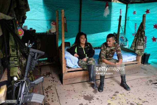 A female FARC guerrilla fighter sits with her partner inside a makeshift quarter allocated for their residence inside a demobilization camp on...