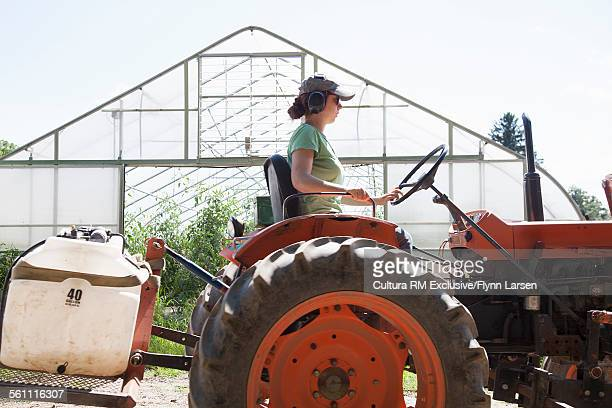 Female farmer driving tractor past greenhouse