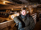 A photograph of a mature woman farmer in a barn with cows.