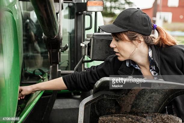 Female farmer repairing tractor