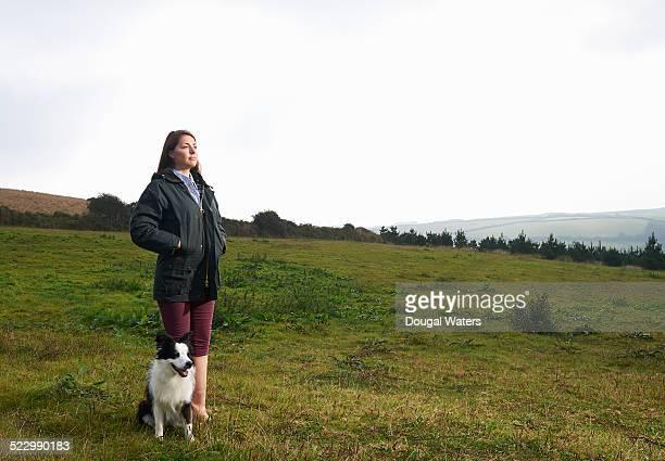 Female farmer standing with dog on farmland.
