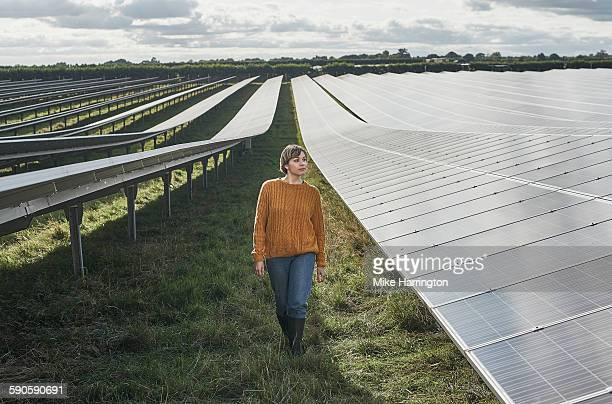 Female farmer walking through solar farm