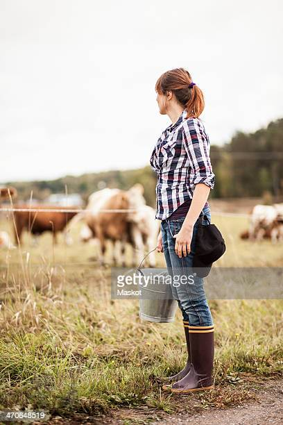 Female farmer with bucket standing on field with animals grazing in background