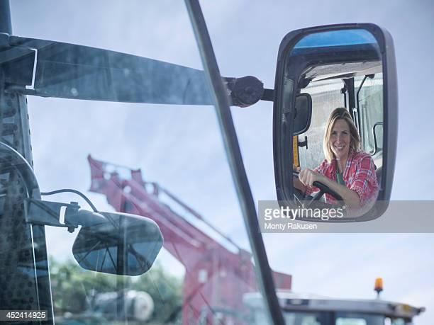 Female farmer's reflection in rearview mirror