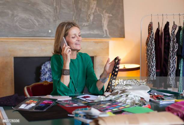 Female fashion designer at her work table, talking on mobile phone