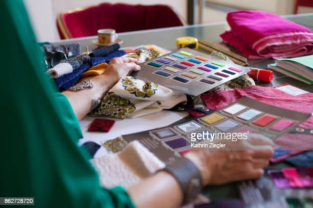 Female fashion designer at her workplace, choosing from fabric color chart