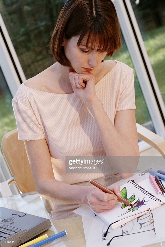Female fashion designer sketching dress in home office : Stock Photo