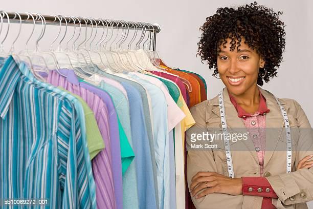 Female fashion designer standing by clothes rack, portrait