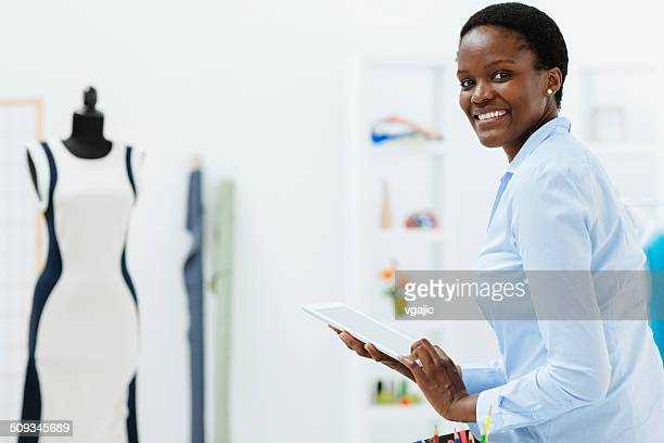 Female fashion designer using digital tablet in office.