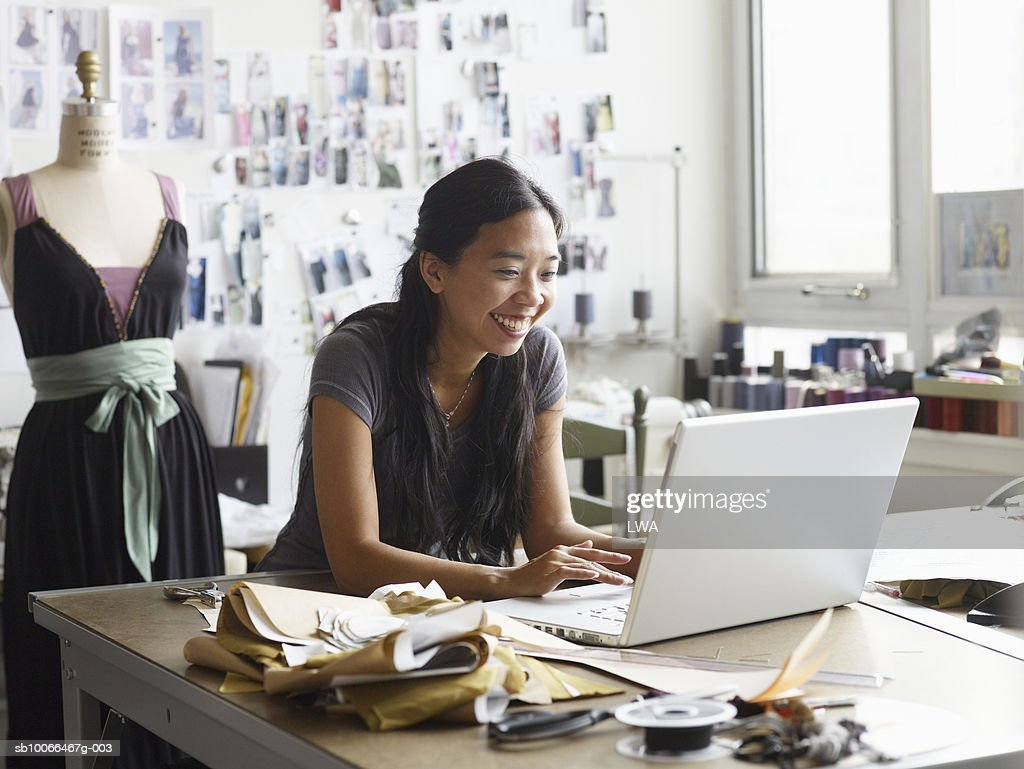 Female fashion designer using laptop in studio, smiling : Stock Photo