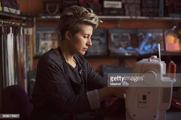 Female fashion designer using sewing machine in studio