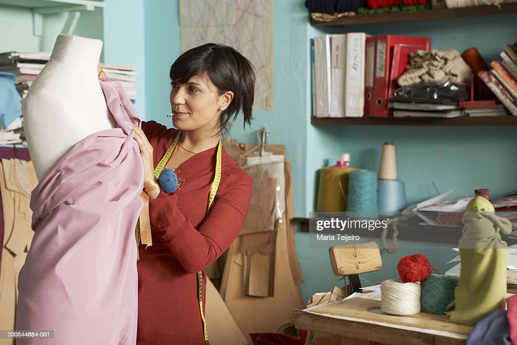 Female fashion designer working on dress on mannequin : Stock Photo
