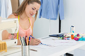 Young female fashion designer working on her designs in the studio
