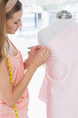 Side view of a beautiful female fashion designer working on pink fabric