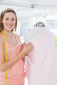 Portrait of a beautiful female fashion designer working on pink fabric