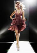 Female fashion model wearing dress on catwalk