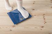 female feet in socks on the floor scales