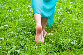 Female feet without shoes are walking on the grass