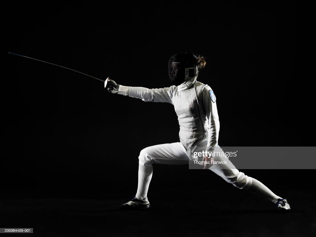 Female (14-16) fencer in defensive pose, side view : Stock Photo