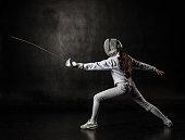 Female fencer wearing white fencing costume isolated on black background