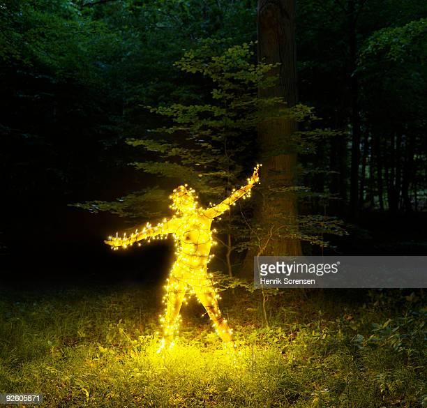 Female figure in wood engulfed in fairy lights