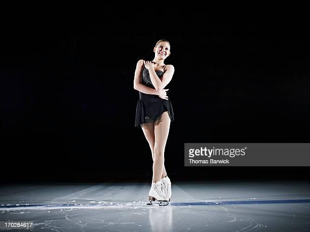 Female figure skater finishing program on ice rink