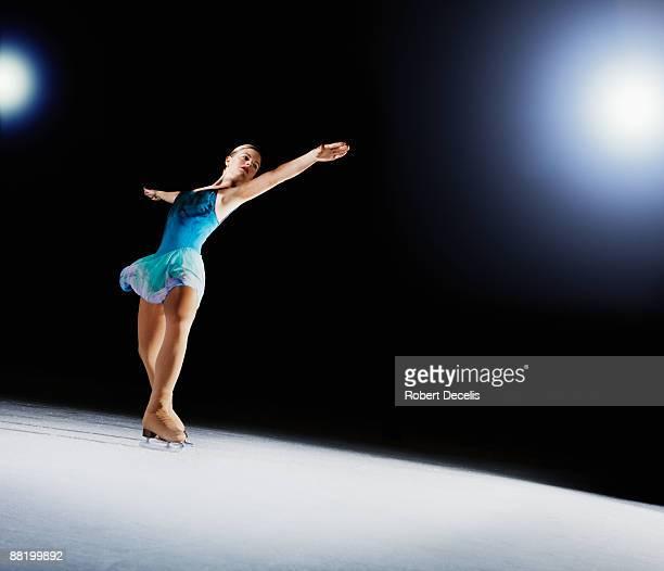 Female figure skater, performing on ice.