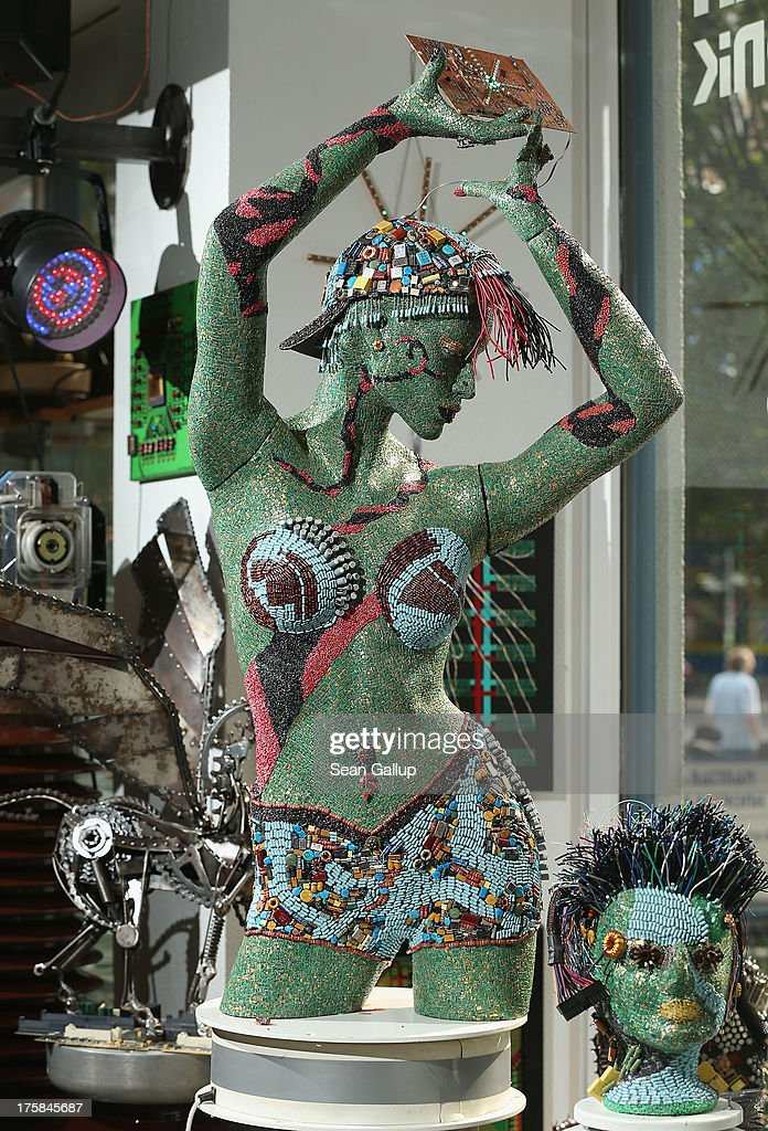 A female figure whose surface is completely covered in electronics junk stands on display at the electronics repair shop owned by Muharrem Batman in Neukoelln disrict on August 8, 2013 in Berlin, Germany. Batman has created a wide variety of busts and even full body sculptures whose outer surfaces are nearly completely covered in electronics capacitors, resistors, bits of circuit boards, CPUs, wiring, keyboards and other scrap he has salvaged from old computers and other devices. Though he says the designs are his own, he admits his sister Ayse and colleague Judith Brun do the much of the actual work. 'I just don't have the patience for it, women can do something like that much better,' he says. He completed his first piece ten years ago, initially solely with the intent of decorating his store, though he has recently launched a website and hopes to have an exhibition.