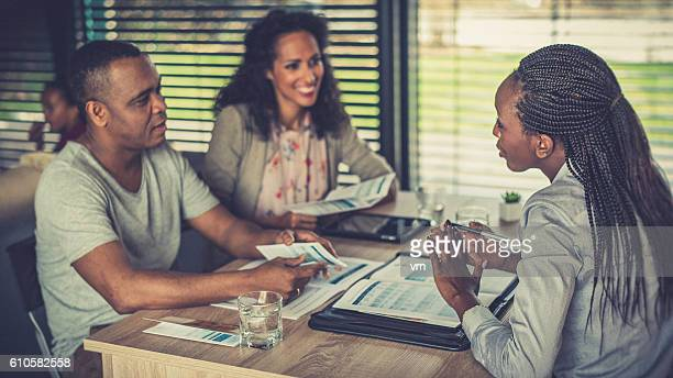 Female financial advisor talking to a couple at home