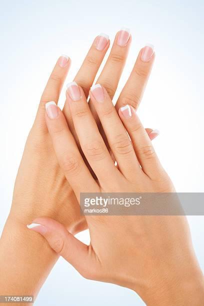Female fingernails over light blue background