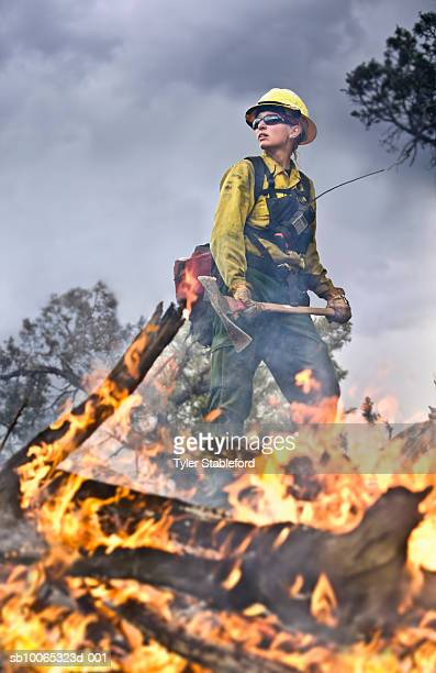 Female fire-fighter holding pickaxe near burning branch