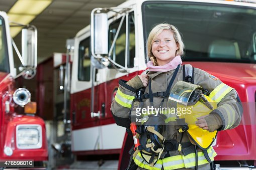 Female firefighter standing in front of fire truck