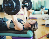 Female fitness instructor lifting weights, wearing headset, side view