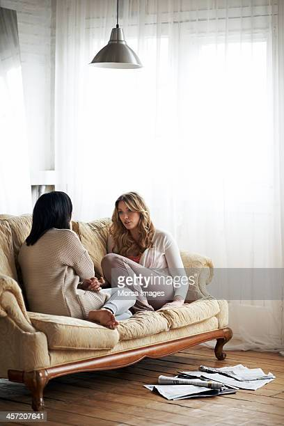 Female flatmates relaxing on sofa