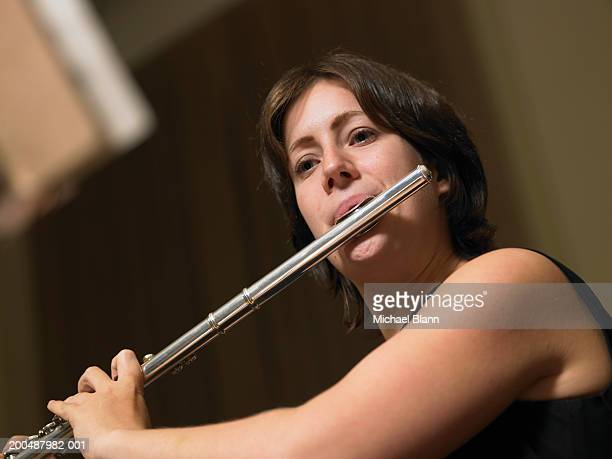 Female flautist playing flute, close-up, low angle view
