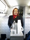 Female Flight Attendant Stewardess Cabin Crew Pushing Beverage Service Cart