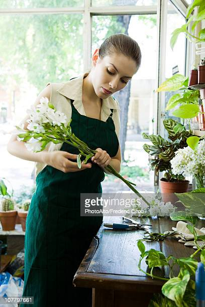 Female florist arranging flowers in shop