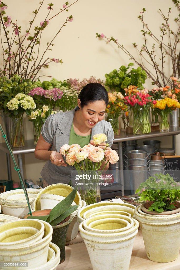Female florist arranging roses : Stock Photo