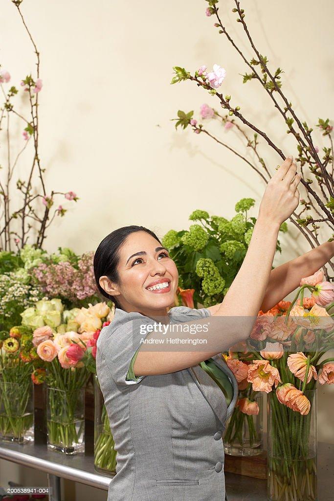 Female florist creating floral arrangement : Stock Photo