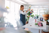 Female florist at work arranging various flowers in bouquet. Woman standing at counter making a bouquet of fresh flowers.