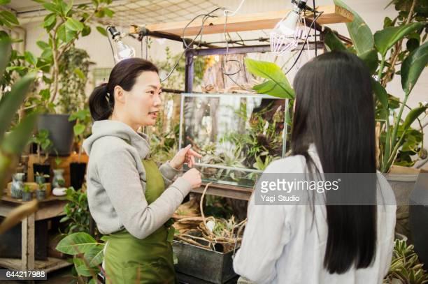 Female florist helping customer in flower shop