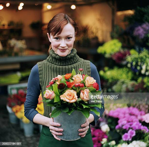 Female florist holding bucket of roses (Rosa sp.), smiling, portrait