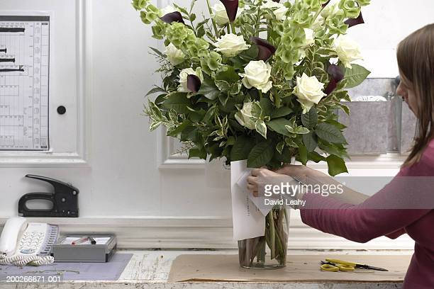 Female florist securing card to bouquet of flowers in vase, side view