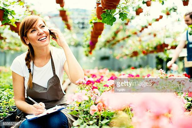 Female Florist Talking On The Phone At Greenhouse.