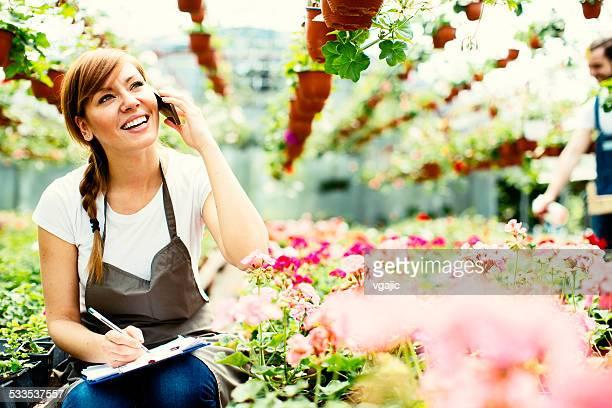 Weibliche Blumenladen sprechen am Telefon im Gewächshaus.