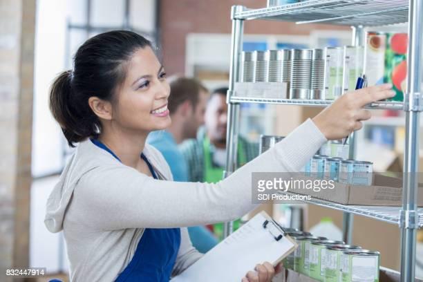 Weibliche Food Bank-Manager organisiert Abstellraum